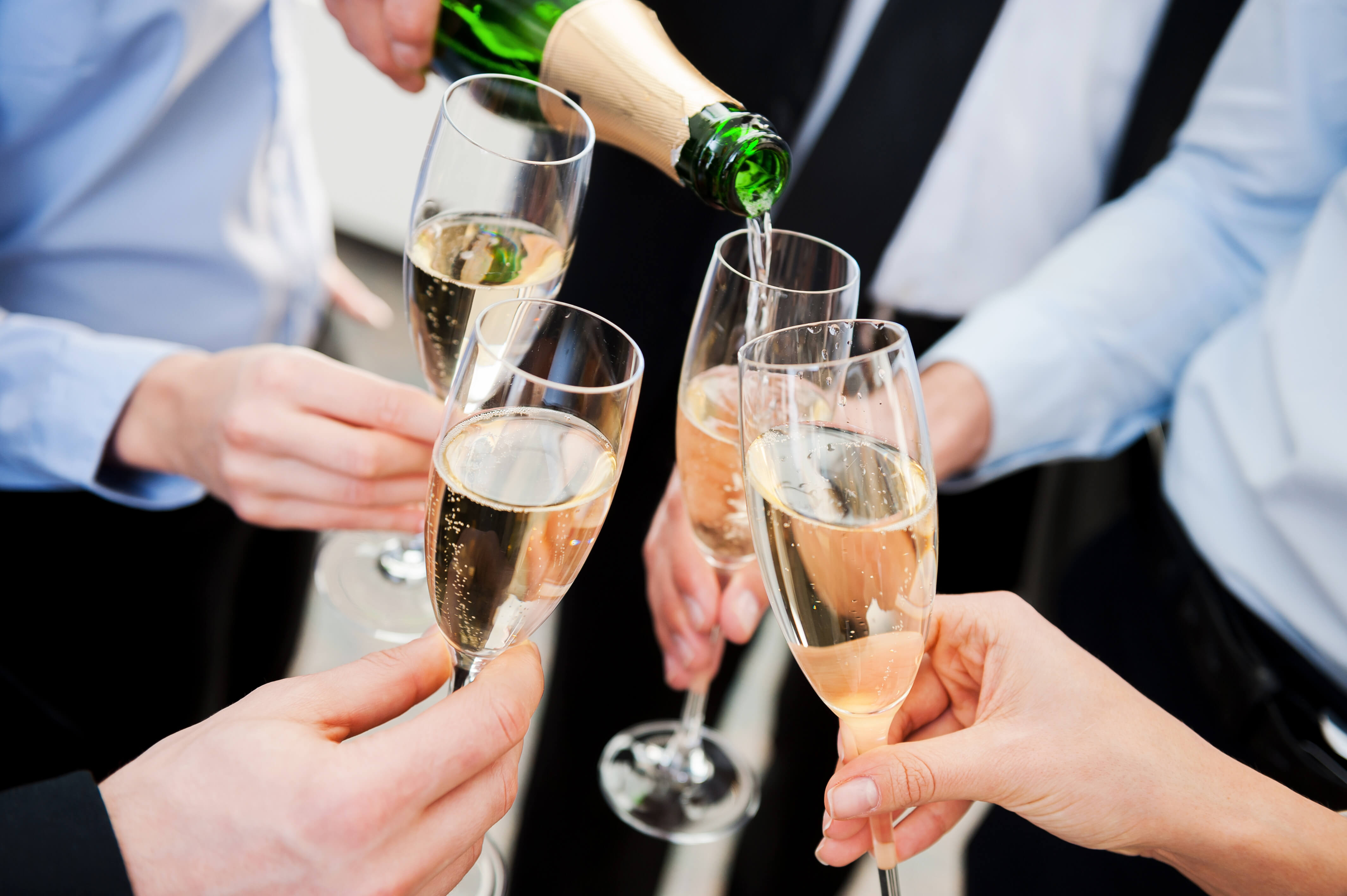 Close-up of business people holding flutes with champagne and toasting